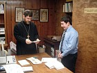 Emery shows Fr. John his prayer book.