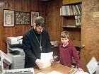 Fr. John helps Luke put his prayer book together.