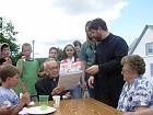 Fr. John Hopko presents a commemorative book to Deacon Sam