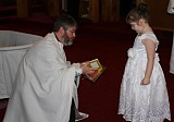 Fr. John presents Caroline with a Liturgy Book and an Icon of her Patron Saint at the conclusion of the Baptism Service