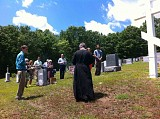 Fr. John and the faithful gather at the Cross at the center of the Parish Cemetery